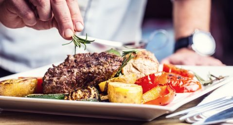 Chef topping steak with herbs.